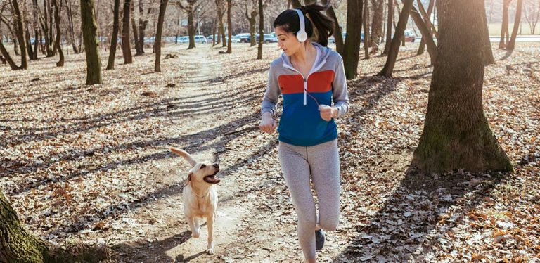 Woman running with dog on forested trail