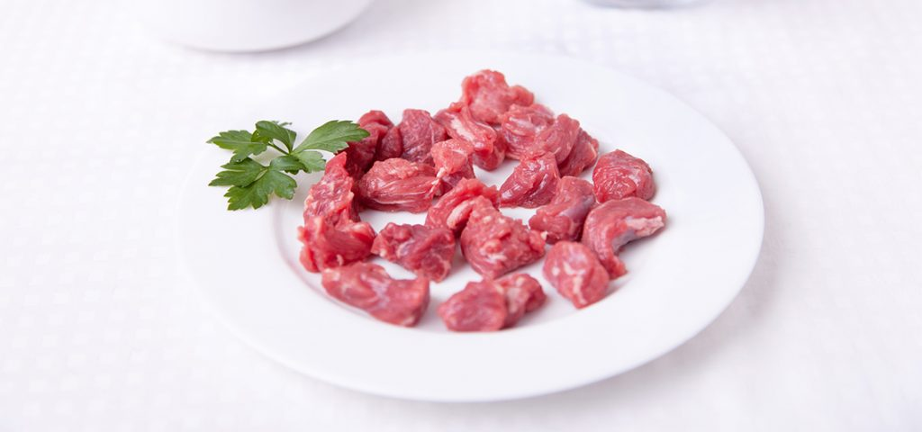 Cut up pieces of raw meat on a plate