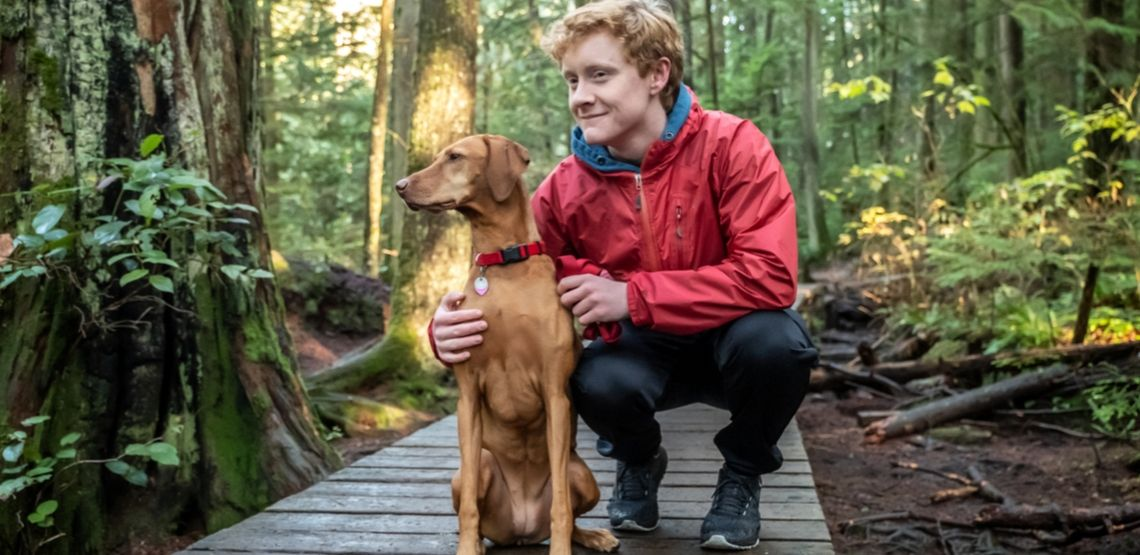 An owner and his dog are taking a break while hiking in the woods.