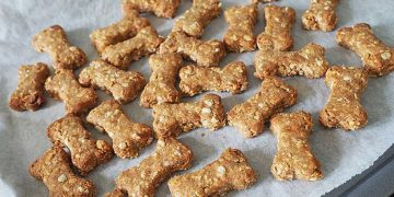 A baking sheet lined with parchment paper and topped with several bone-shaped DIY dog treats.